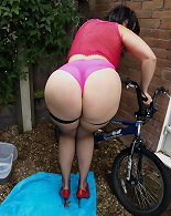 Slut MILF washing bike outdoors in her booty shorts and stockings