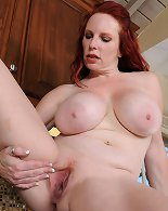 Redheaded and busty Red Vixen plays with her massive fun bags