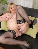 Thick milf in stockings plays with her shaved pussy
